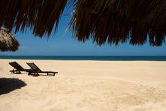 Tropische Ansicht eines Strandes mit Regenschirmen lizenzfreie stockfotos