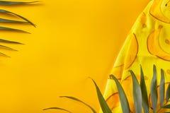 Tropische bladeren met strandhanddoek op gele achtergrond Minimaal concept Vlak leg De ruimte van het exemplaar royalty-vrije stock afbeelding