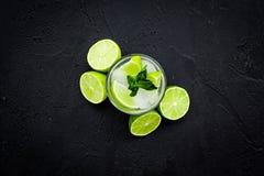 Tropische cocktail Drank dievan de vrouwen houdt Glas van mojito met plakken van kalk, munt, ijsblokjes op zwarte achtergrond Royalty-vrije Stock Afbeeldingen
