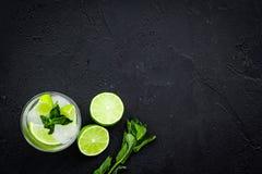 Tropische cocktail Drank dievan de vrouwen houdt Glas van mojito met plakken van kalk, munt, ijsblokjes op zwarte achtergrond Royalty-vrije Stock Foto