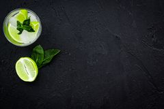 Tropische cocktail Drank dievan de vrouwen houdt Glas van mojito met plakken van kalk, munt, ijsblokjes op zwarte achtergrond Stock Afbeeldingen