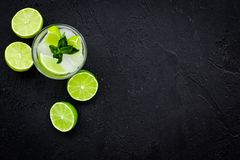 Tropische cocktail Drank dievan de vrouwen houdt Glas van mojito met plakken van kalk, munt, ijsblokjes op zwarte achtergrond Stock Foto