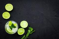 Tropische cocktail Drank dievan de vrouwen houdt Glas van mojito met plakken van kalk, munt, ijsblokjes op zwarte achtergrond Stock Foto's