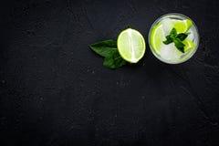 Tropische cocktail Drank dievan de vrouwen houdt Glas van mojito met plakken van kalk, munt, ijsblokjes op zwarte achtergrond Royalty-vrije Stock Fotografie