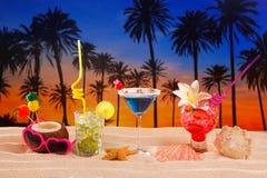 Tropische cocktails op witte zandmojito op zonsondergangpalmen Stock Fotografie