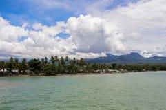 Tropische eilandmening met palmen en verre berg Warme overzees met strandlijn en bos Royalty-vrije Stock Foto's