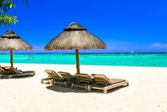 Tropische Feiertage - Strandstühle und -regenschirme in Mauritius-Insel stockfotos