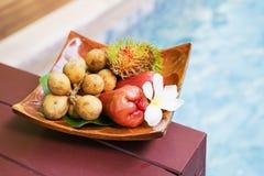Tropische Früchte in der Weichzeichnung auf hölzernem Behälter nahe Swimmingpool Lizenzfreie Stockfotografie