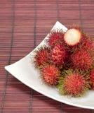 Tropische Früchte Rambutan mit Platte auf Bambusmatte Stockbild