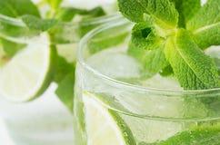 Tropische frische grüne kalte Cocktailnahaufnahme mit Minze, Kalk, Eis, Stroh, Wasser fällt, Blasen, Unschärfe Lizenzfreies Stockfoto