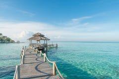 Tropische Hütte und Holzbrücke am Ferienzentrum Junge Frau auf dem Strand von Formentera-Insel