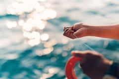 Tropische hand die in zonsondergangtijd vissen Vislijn en hand, vage overzeese achtergrond stock foto