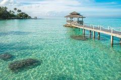 Tropische Hütte und Holzbrücke am Ferienzentrum Junge Frau auf dem Strand von Formentera-Insel Stockfoto