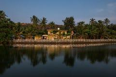 Tropische Küste mit Haus und Palmen Stockbild