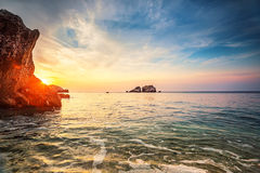 Tropische kleurrijke zonsondergang bij het stenenstrand Stock Foto's