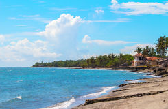 Tropische Landschaft mit See-, Strand- und Palme Sandstrandansicht mit Palmen und Haus Lizenzfreies Stockfoto