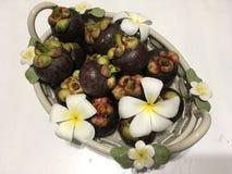 Tropische Mangostanfruchtfrüchte im keramischen Korb, verziert mit Frangipaniblumen stockbilder