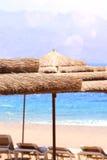 tropische overzees en ligstoelen onder paraplu's De zomerreis en vakantieconcept Stock Fotografie