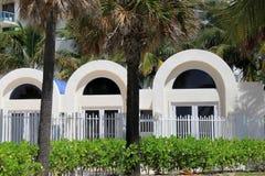 Tropische Palmen vor gewölbten Eingängen Stockfotos