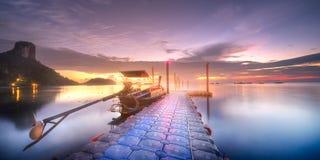 Tropische rustige kust en pijler in stralen van dageraad stock foto's