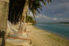 Tropische Strand-Hängematte unter Palmen Stockfotografie