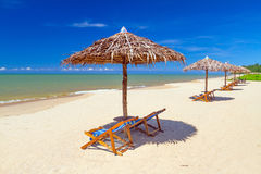 Tropische Strandlandschaft mit Sonnenschirm und Klappstühlen Lizenzfreie Stockfotos