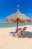 Tropische Strandlandschaft mit Sonnenschirm und Klappstühlen Stockbild