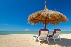 Tropische Strandlandschaft mit Sonnenschirmen Lizenzfreie Stockbilder