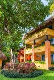 Tropische Urlaubshotelgebäude in den orange und gelben Farben umfasst mit Palmblattdach Stockfoto