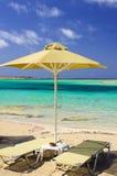 Tropische vakantie - bedden en paraplu op een strand stock foto's