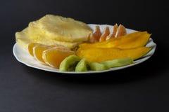Tropische vruchten, kiwi, mango, ananas, sinaasappel en mandarin ora stock foto