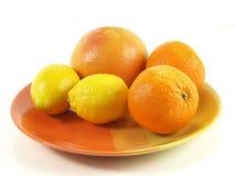 Tropische vruchten op oranje plaat, geïsoleerdes studio. Royalty-vrije Stock Fotografie