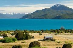 Tropischer blauer See General Carrera, Chile mit Landschaftsbergen und Scheune stockfotografie
