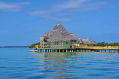 Tropischer Erholungsort mit mit Stroh gedeckten Bungalows über Wasser Stockfotografie