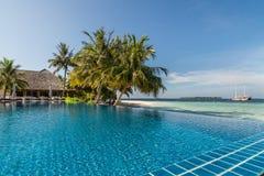 Tropischer Erholungsort Poolside mit Seehintergrund lizenzfreie stockbilder