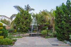 Tropischer Garten mit Wasserspray und Regenschirm in der Stadt von NaI Lizenzfreie Stockbilder