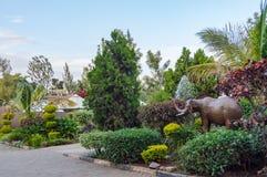 Tropischer Garten mit Wasserspray und Regenschirm und ein Elefantst. Lizenzfreie Stockbilder