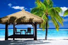 Tropischer Gazebo mit Stühlen auf erstaunlichem Strand stockfotografie