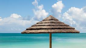 Tropischer Meerblick mit Strand-Regenschirm u. sonnigem Himmel stockfoto