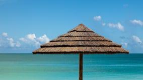 Tropischer Meerblick mit Strand-Regenschirm und Himmel lizenzfreies stockbild