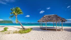 Tropischer natürlicher Strand auf Samoa-Insel mit Palme und fale, Stockfotos