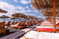 Tropischer Ozean-Strand-deckte orange weißer Verfolgungs-Aufenthaltsraum Regenschirme mit Stroh Stockfotografie