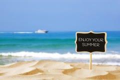 Tropischer sandiger Strand und leere hölzerne Tafel unterzeichnen mit Zitat Stockfotos
