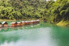 Tropischer See mit sich hin- und herbewegenden Häusern stockfotografie