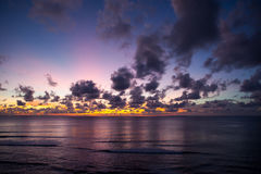Tropischer Sonnenuntergang in Meer mit Wolken Stockfotografie