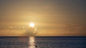 Tropischer Sonnenuntergang mit der Sonne, die in die Wolke einstellt lizenzfreies stockbild