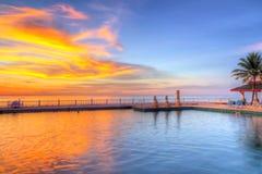 Tropischer Sonnenuntergang am Swimmingpool Stockbilder
