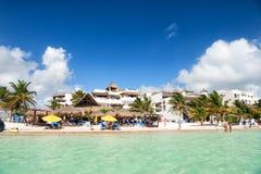 Tropischer Strand auf Costamaya, Mexiko See- oder Ozeanwasser mit Leuten und Regenschirmen auf Sand Hotel und grüne Palmen auf so Stockfotografie
