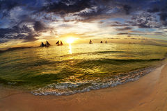 Tropischer Strand bei Sonnenuntergang Stockbilder
