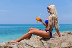 Tropischer Strand des dünnen blonden langhaarigen Cocktails des Frauenbikinis orange Lizenzfreie Stockfotografie
